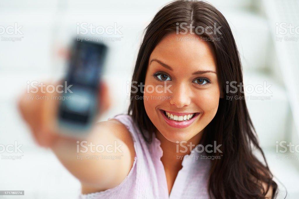 Charmante Frau holding Handy in der hand und Lächeln Lizenzfreies stock-foto
