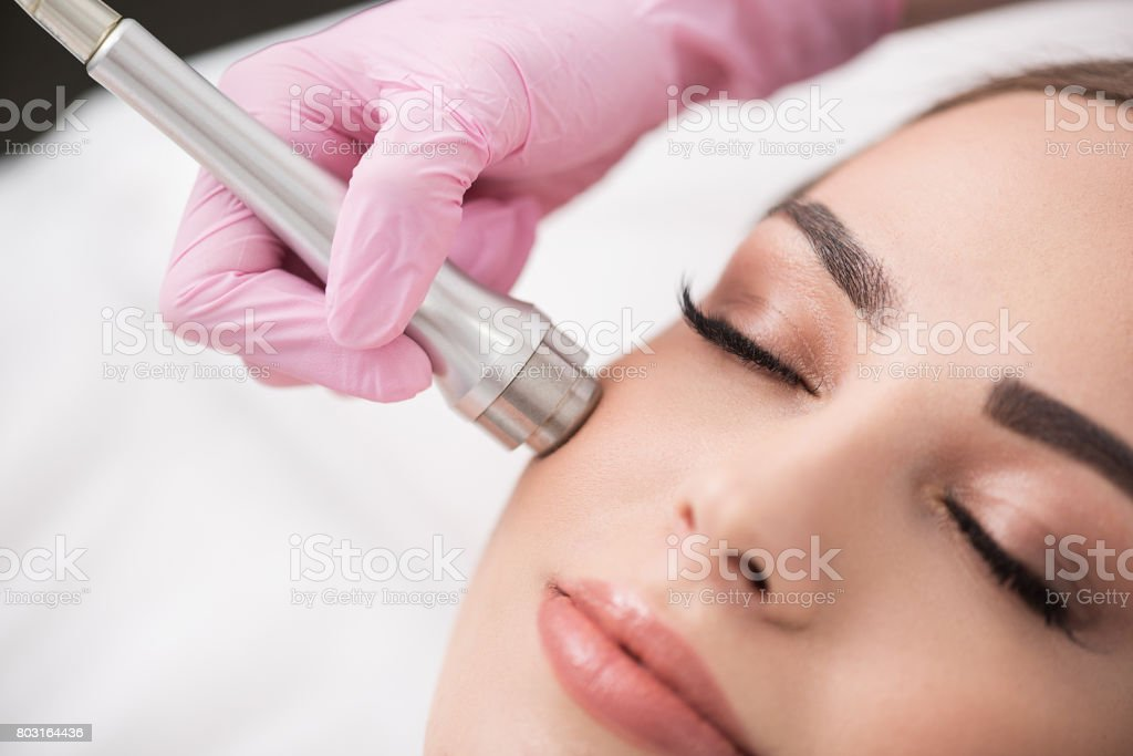 Charming lady is getting cosmetic treatment in spa stock photo