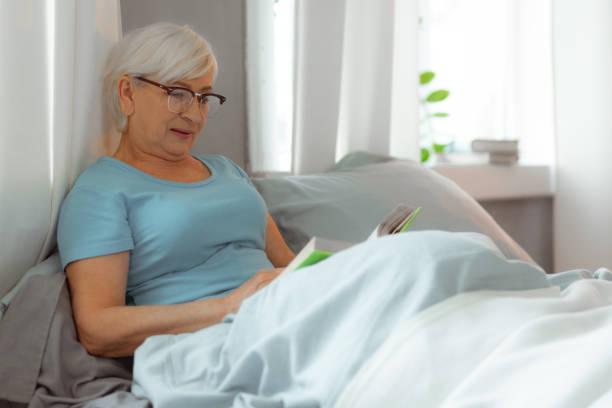 charmante dame liegt im bett und liest ein buch. - sexy granny stock-fotos und bilder