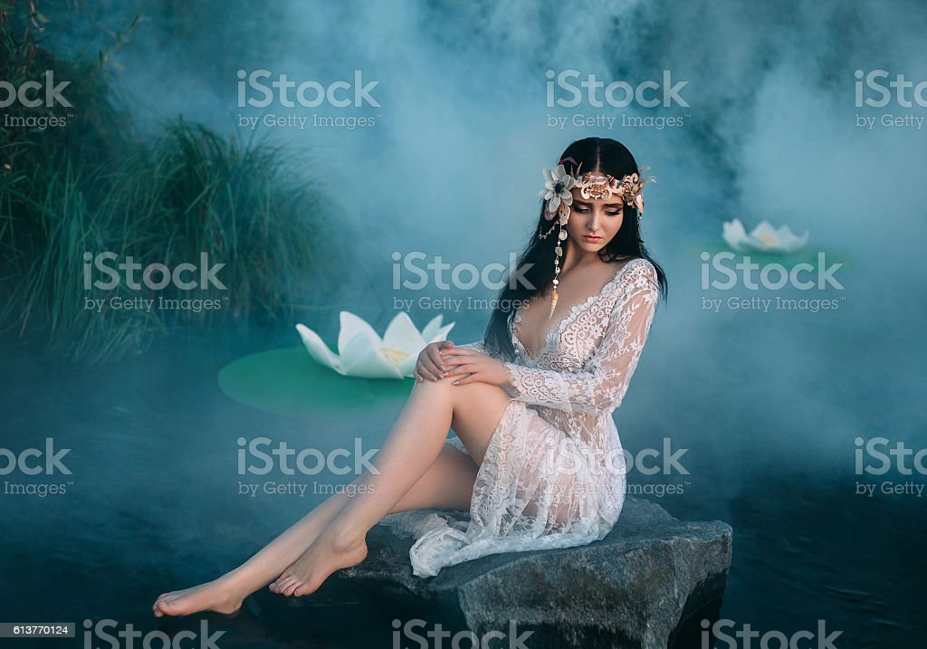 Charming lady sitting on a  rock in middle of lake stock photo