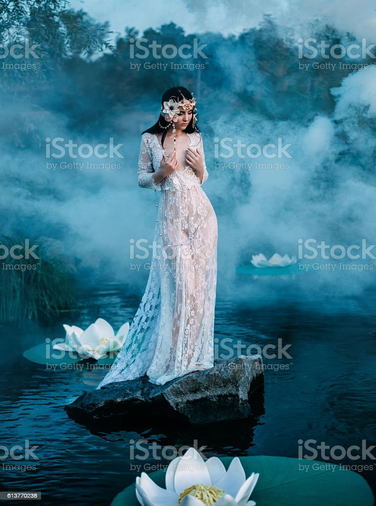 Charming lady, standing on a  rock in middle of lake stock photo