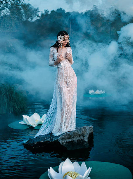 charming lady, standing on a  rock in middle of lake - elfen fantasy stock-fotos und bilder