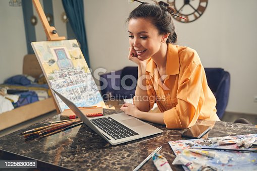 Attractive young woman chatting with friend online and smiling while sitting at the table in home art studio