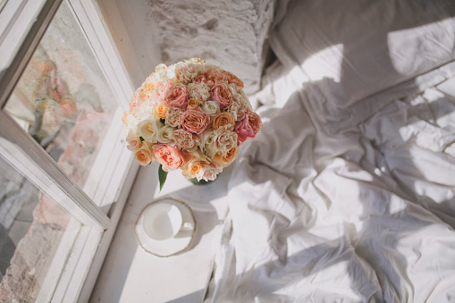 A charming large bouquet of roses and a white tea cup is on the windowsill next to the bed.
