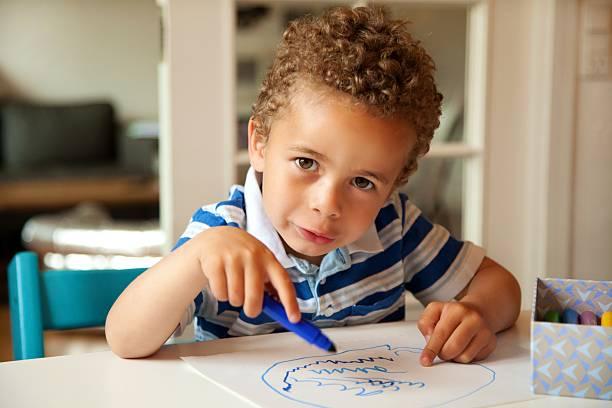 süße kleine junge lebhaften farben an seinem schreibtisch - scribble stock-fotos und bilder