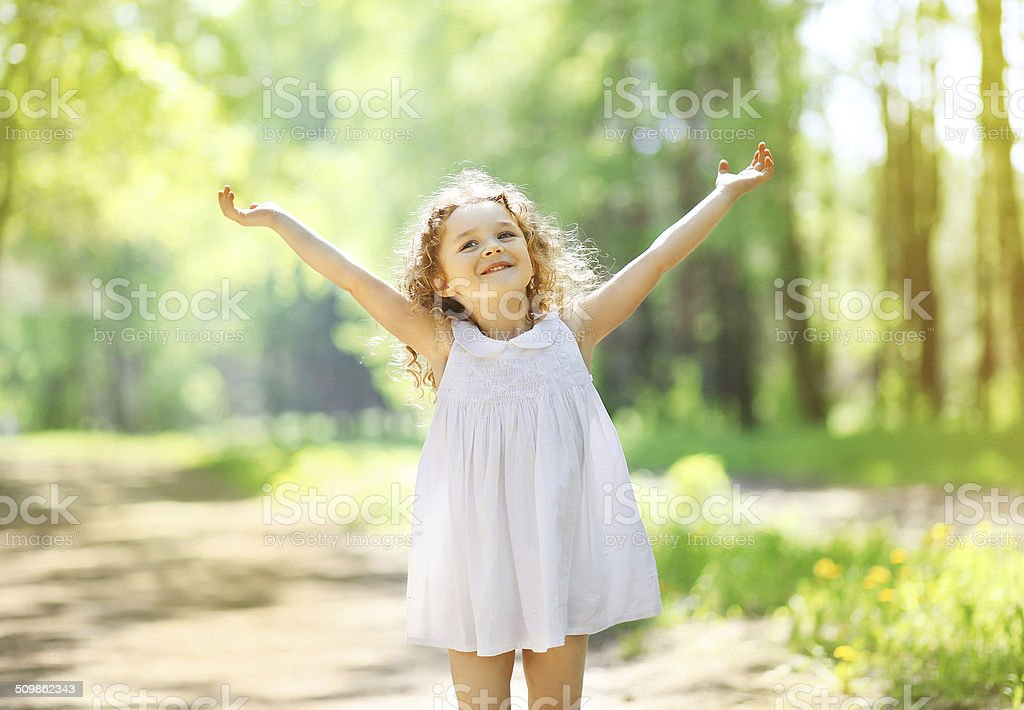 Charming little girl enjoying summer sunny day, raises his hands stock photo