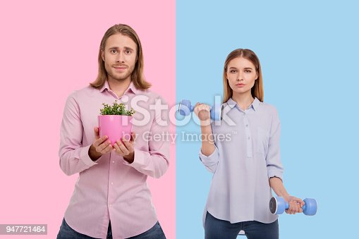 istock Charming man holding plant while woman exercising with dumbbells 947721464