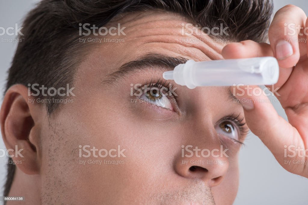Charming man is pouring drops in eyes stock photo