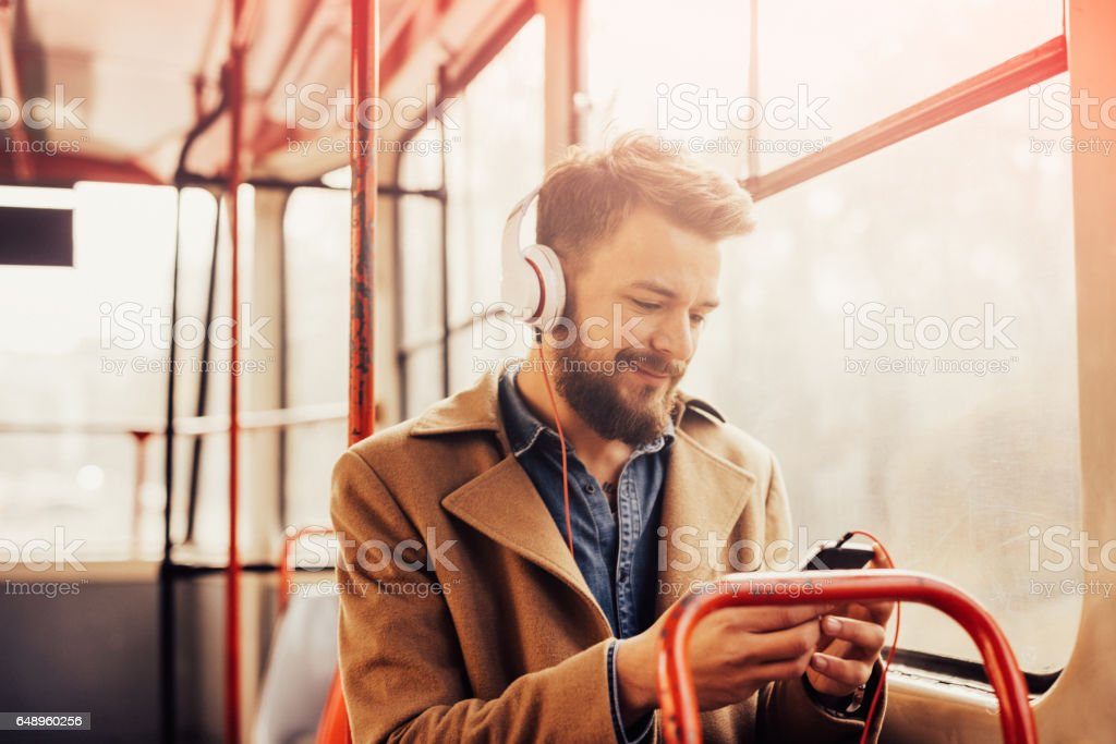 Charming man listening to music with headphones on a public bus stock photo