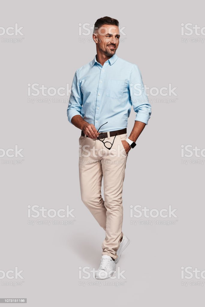 Charming man. Full length of handsome young man smiling and keeping hand in pocket while walking against grey background Adult Stock Photo