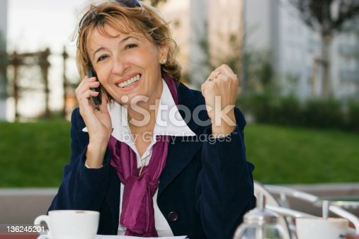 Charming mature businesswoman sitting in a Cafe and talking by mobile.