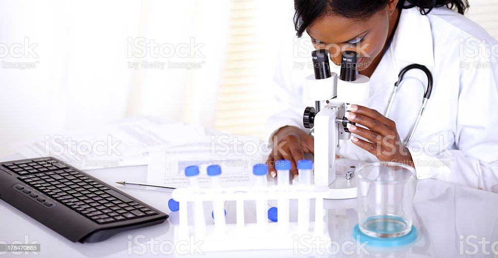 Charming medical doctor woman using a microscope royalty-free stock photo