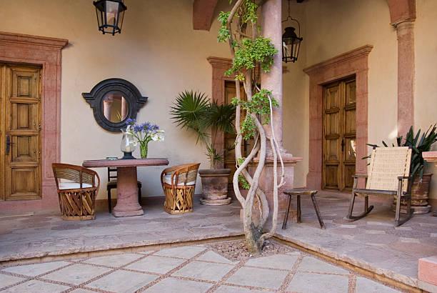charmante mexikanische innenhof mit tischen und stühlen - mexikanische möbel stock-fotos und bilder