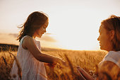 Charming mother and her daughter posing in a wheat field against the sunset