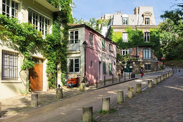 Charming old street of Montmartre hill. Paris, France Paris, France - July 06, 2016: The charming old street of Montmartre hill in the sunny summer evening in backlit sunset sunbeam are full of art galleries, cafes and shops to walk about. ile de france stock pictures, royalty-free photos & images