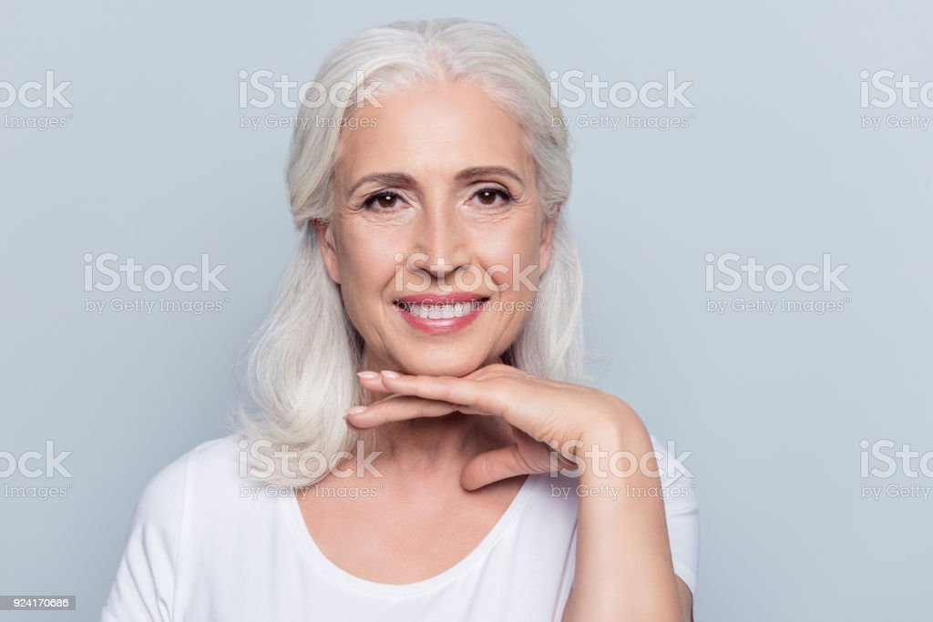 Charming old woman holding hand under chin with beaming smile looking at camera over gray background stock photo