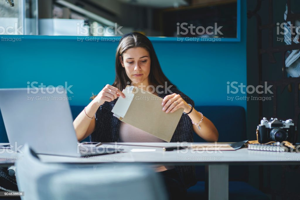 Charming pensive employee of trading company receiving business letter with documentation sitting at working space with laptop computer,concentrate  secretary assistant opening envelope with papers stock photo