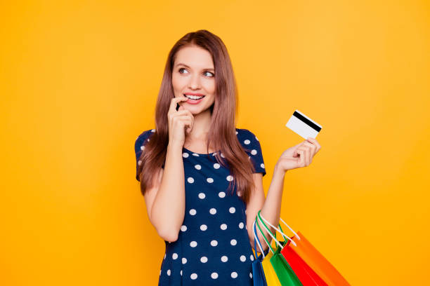 Charming pretty attractive sexy girl having bank card in hand and finger near lips, thinking about buys, what she need and want, standing over yellow background stock photo