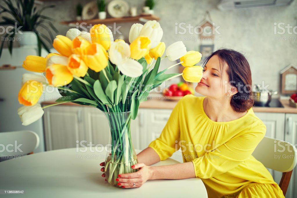 Charming, pretty girl is holding a big tulip bouquet in hands stock photo