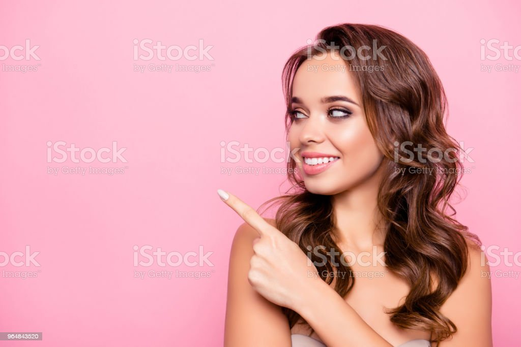 Charming, pretty, nice, attractive, shirtless girl with curly hair and beaming smile pointing to copy space with forefinger, looking at product, isolated over pink background royalty-free stock photo