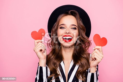 Charming pretty nice, comic, funny, modern, cheerful, laughing girl in black and white jacket having two small paper heart in hands, isolated on pink background
