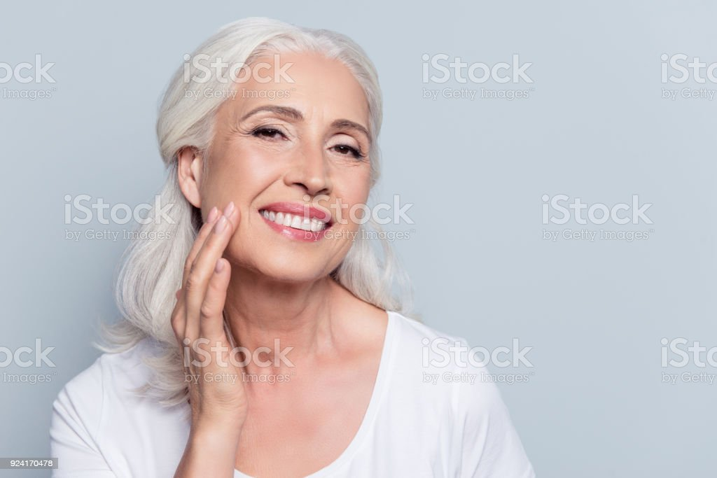 Charming, pretty, old woman touching her perfect soft face skin with fingers, smiling at camera over gray background, using day, night face cream, cosmetology procedures stock photo