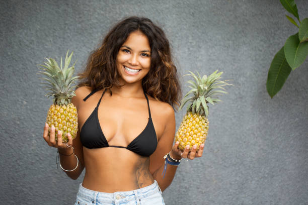 Charming Pretty Woman In Bra With Pineapples stock photo