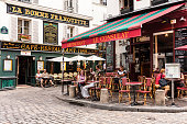 Paris, France - July 06, 2017: The charming restaurant Le Consulat on the Montmartre hill. Parisians and tourists enjoy food and drinks. Montmartre with traditional French cafes and art galleries is one of the most visited landmarks in Paris.