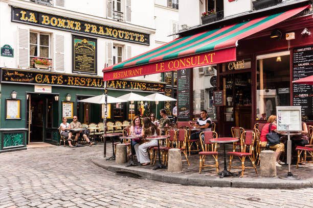 Charming restaurant Le Consulat on the Montmartre hill. Paris, France Paris, France - July 06, 2017: The charming restaurant Le Consulat on the Montmartre hill. Parisians and tourists enjoy food and drinks. Montmartre with traditional French cafes and art galleries is one of the most visited landmarks in Paris. french culture stock pictures, royalty-free photos & images