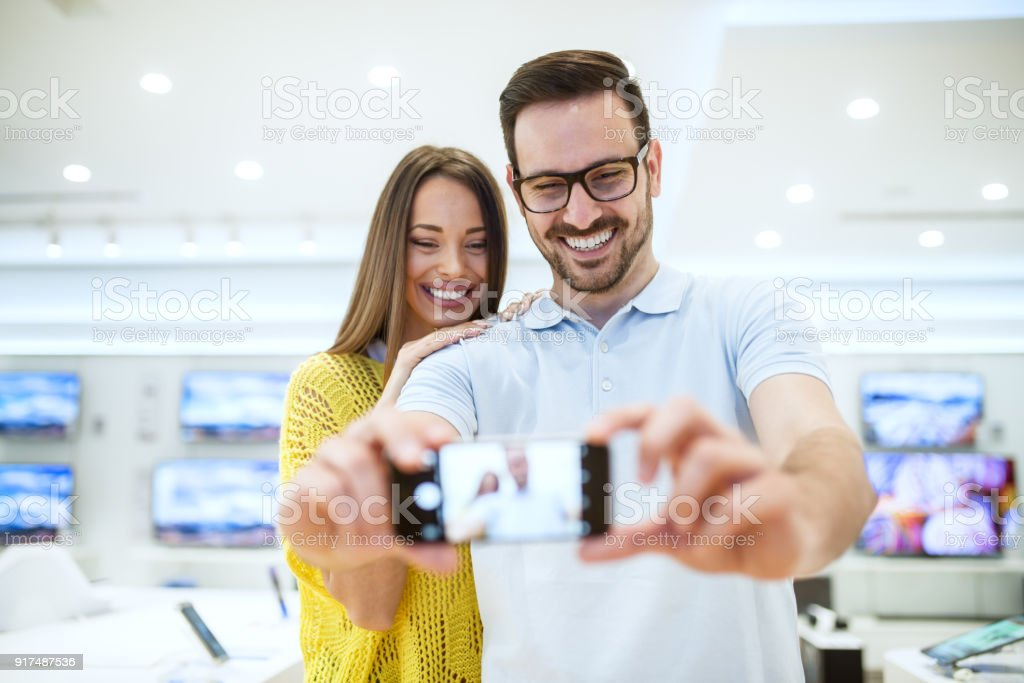 Charming satisfied smiling young love couple testing a mobile camera in a modern tech store. stock photo