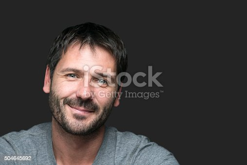 istock charming smiling man portrait isolated on gray 504645692