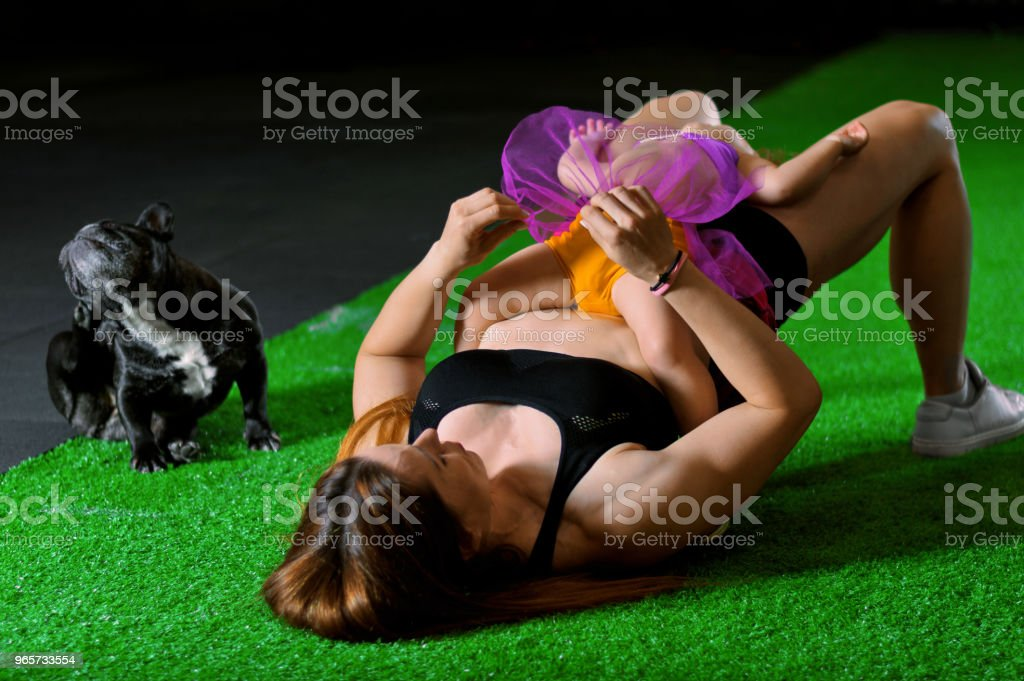 Charming sports mom plays in the gym with her little daughter and a French bulldog. - Royalty-free Activity Stock Photo
