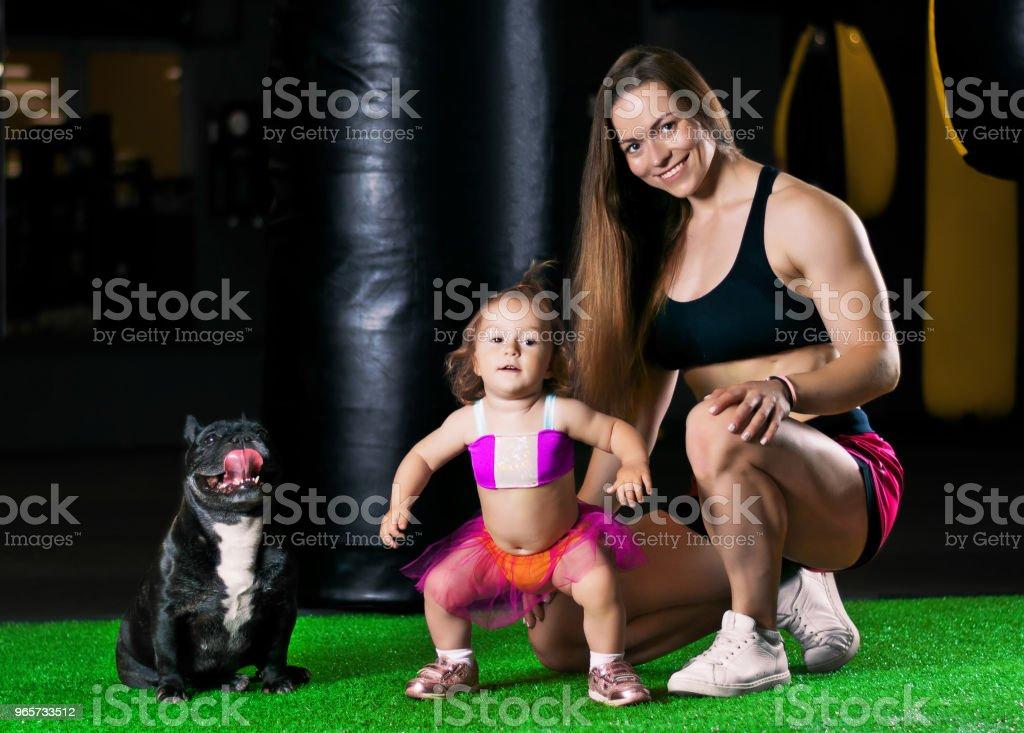 Moeder-treinen van de charmante sporten in de fitnessruimte met haar dochtertje en een Franse bulldog. - Royalty-free Actieve levenswijze Stockfoto
