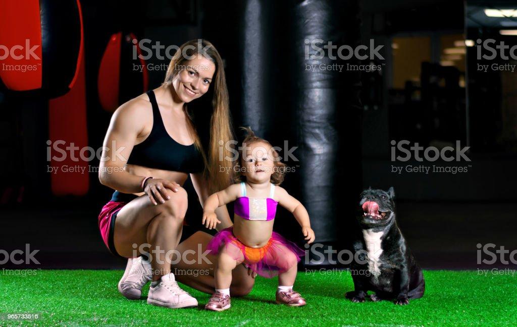 Moeder-treinen van de charmante sporten in de fitnessruimte met haar dochtertje en een Franse bulldog. - Royalty-free Begrippen Stockfoto