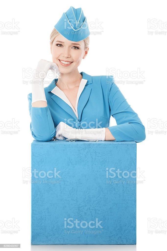Charmante Stewardess vereinbart werden ganz In blauer Uniform und Koffer auf Weiß – Foto