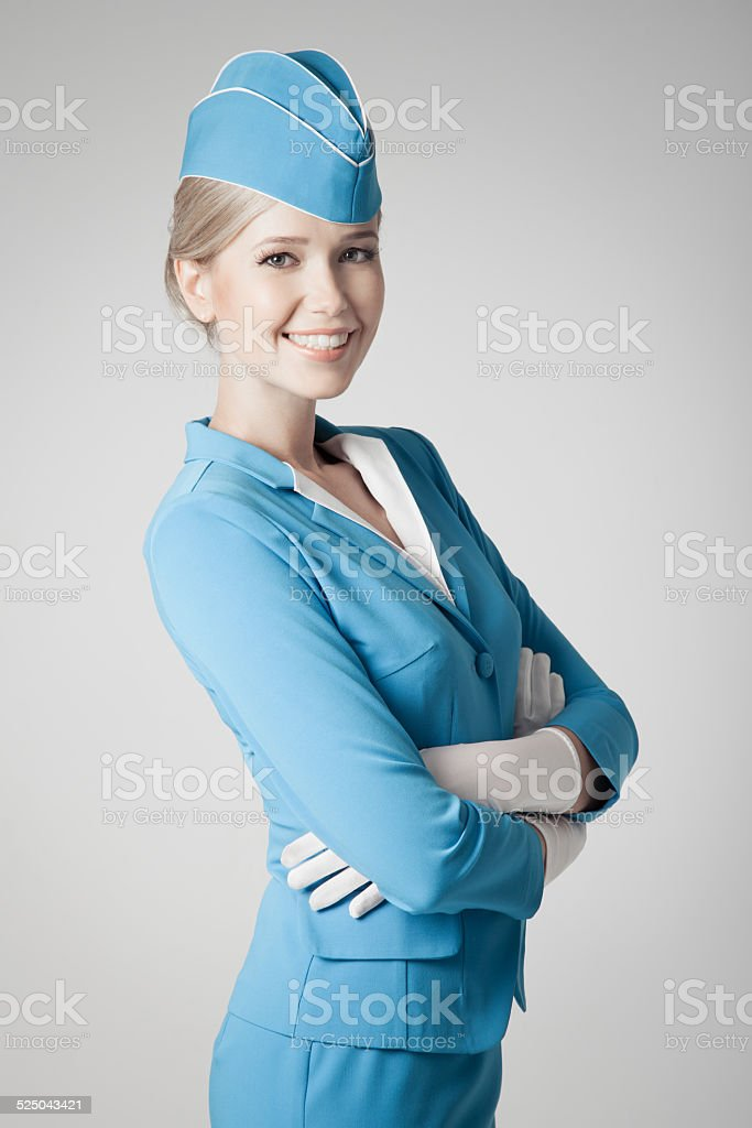 Charming Stewardess Dressed In Blue Uniform On Gray Background stock photo