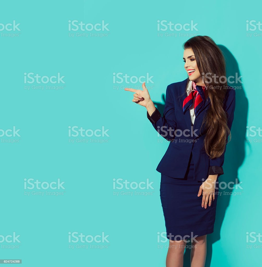 Charming Stewardess  In dark Blue Uniform Pointing The Finger stock photo