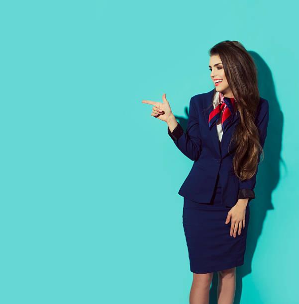 Charming Stewardess  In dark Blue Uniform Pointing The Finger - foto de stock