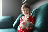 Portrait of smiling beautiful child holding piggy bank sitting on sofa indoors. Lovely blonde kid saving up for future. Girl in red dress. Childhood and happiness concept