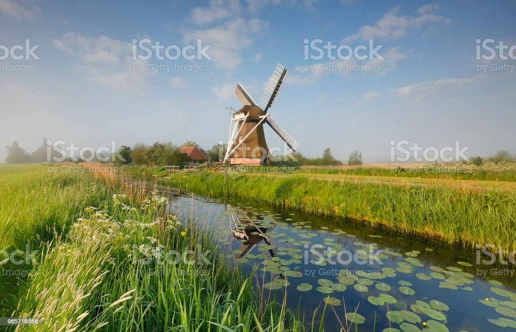 charming windmill by river over blue sky in morning - Royalty-free Agricultural Field Stock Photo