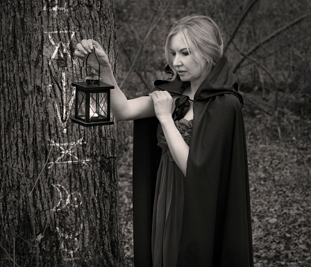Charming witch with lantern by the tree with magic symbols