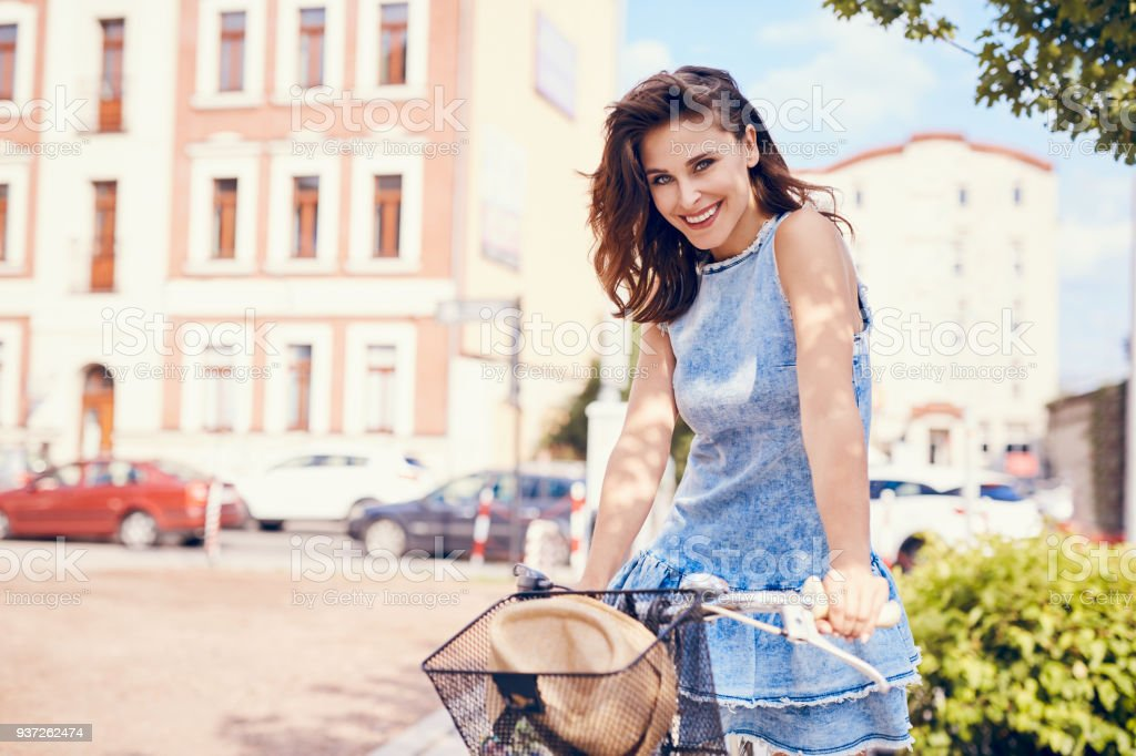 Charming woman on bike in city, during summer stock photo