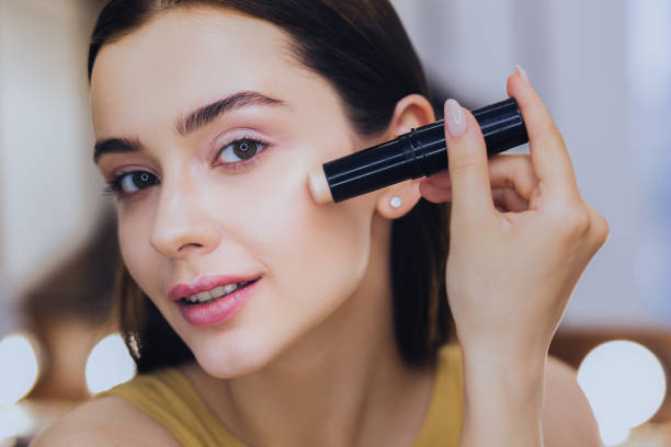 charming woman using concealer stick while putting makeup on - bastone foto e immagini stock