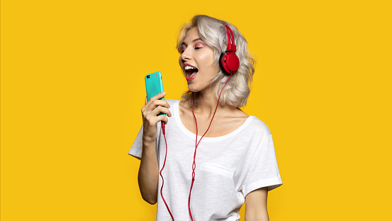 Portrait of happy cute girl listening to music and singing in mobile phone. Pretty lady wearing modern red headphones. Technology and fun concept. Copy space in right side. Isolated on yellow