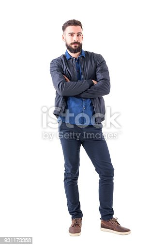 931173966istockphoto Charming young adult male in dark blue bomber jacket with crossed hands looking at camera. 931173358