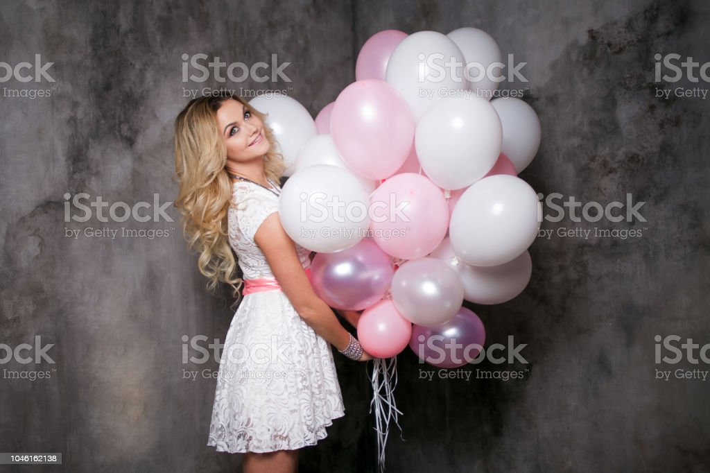 Charming young blonde in a white dress with pink balloons, at the party. stock photo