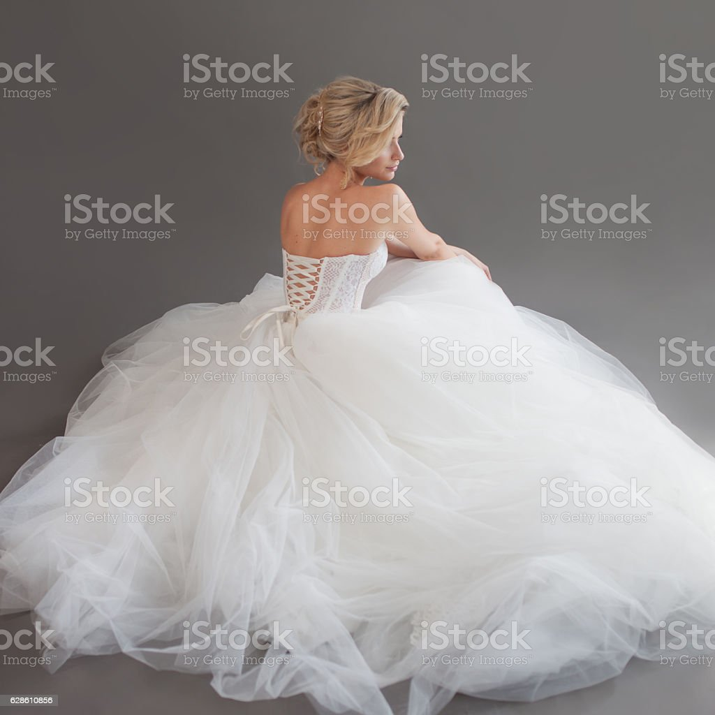 Charming young bride in luxurious wedding dress. Pretty girl in stock photo