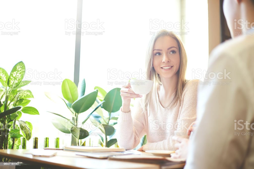Charming young businesswoman talking with unrecognizable colleague at table in cafe, drinking coffee and smiling royalty-free stock photo