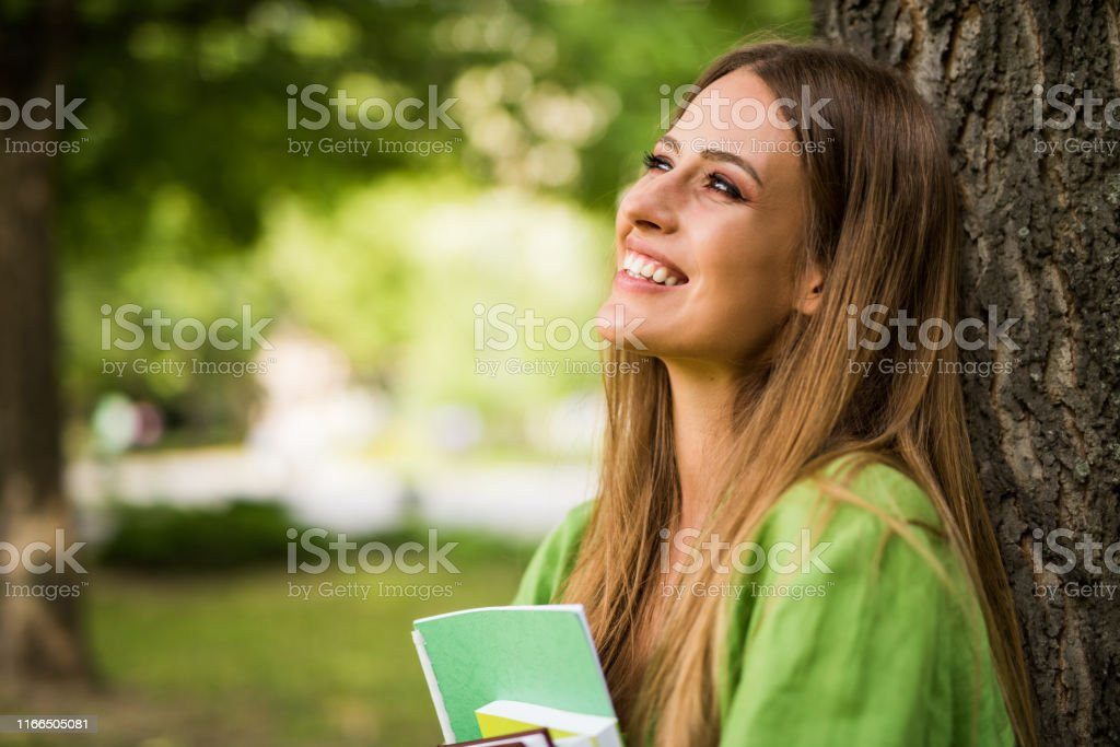 Charming young college girl day dreaming.