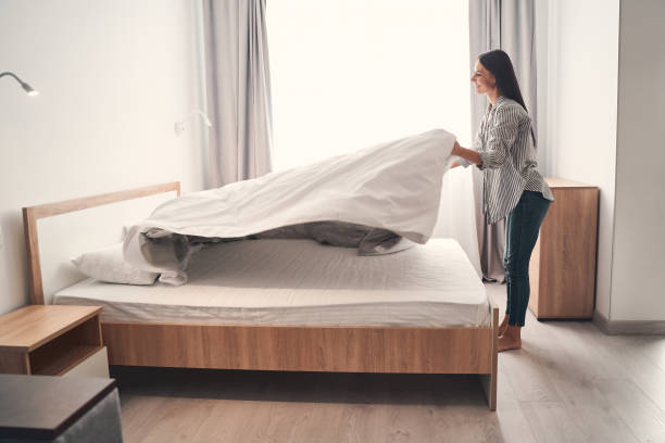 Charming young female person making her bed stock photo